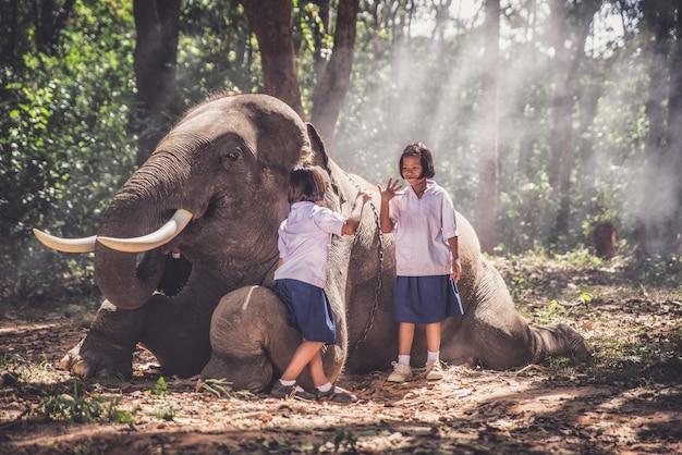 Filles thaïlandaises jouant après l'école dans la jungle près de leur ami éléphant