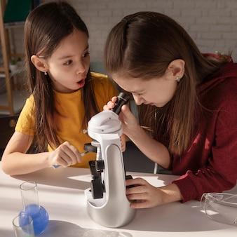 Filles de tir moyen apprenant avec microscope