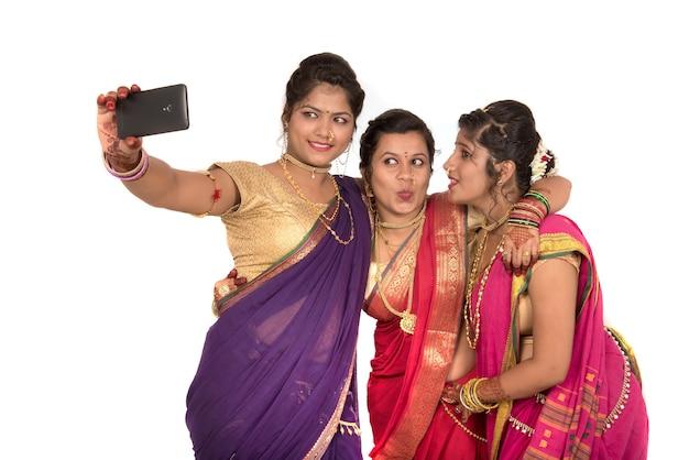 Filles traditionnelles indiennes prenant selfie avec smartphone sur blanc