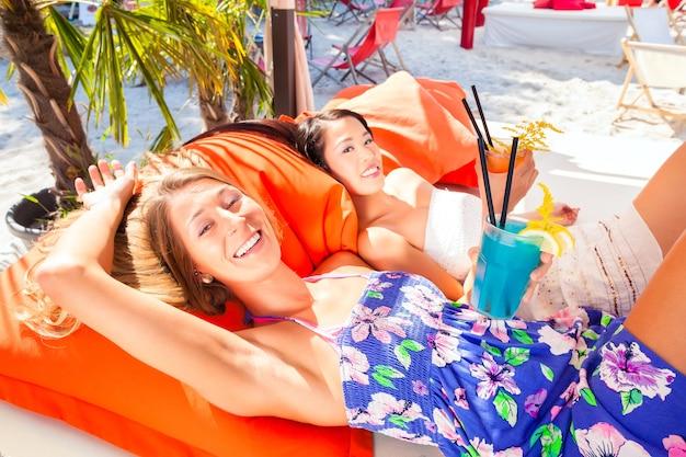 Filles en transats sonores au bar de la plage avec des boissons
