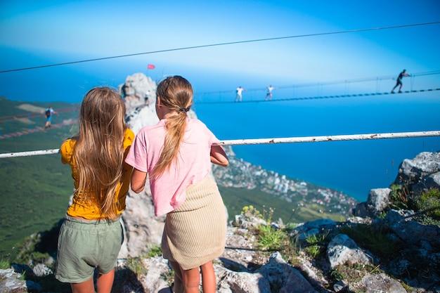 Filles traversant le gouffre sur le pont de corde