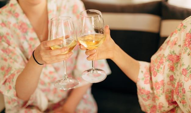 Les filles trinquent en robes de champagne