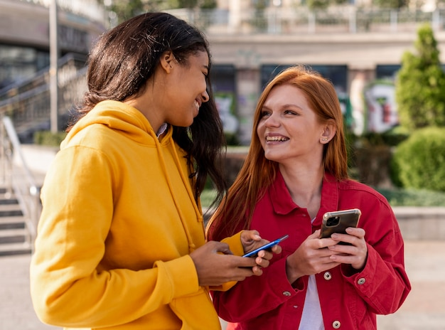 Filles vérifiant leurs téléphones à l'extérieur