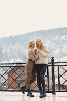 Filles en vêtements légers. café d'hiver sur le balcon. des femmes heureuses ensemble.
