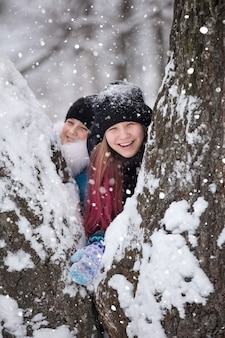Des filles vêtues de vestes chaudes et de chapeaux jouent dans un parc d'hiver avec un chien en promenade