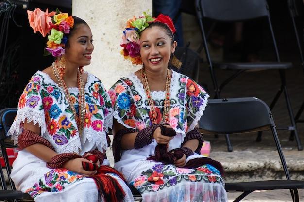 Filles yucatèques se parlent en attendant son tour de se produire dans le festival de la ville.