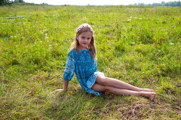Une fillette de 10 ans vêtue d'une robe bleue est assise sur un champ d'herbe et de fleurs, longues jambes nues, pieds nus