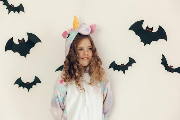 Une fillette de 9 ans en pyjama kigurumi se tient près d'un mur décoré de décorations d'halloween.