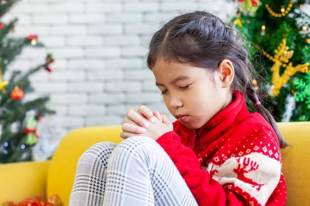 Une fillette asiatique mignonne a fermé les yeux et a plié la main pour prier lors de la fête de noël