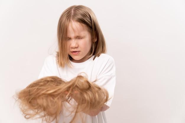 Une fillette bouleversée tient dans les mains les cheveux coupés après avoir coupé sur un fond blanc. signifie prendre soin des cheveux des enfants. salon de beauté pour enfants.
