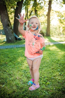 Fillette de deux ans tachée de couleurs contre la pelouse verte