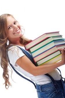Fillette portant une pile de livres
