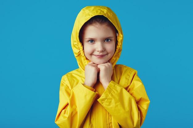Une fillette porte un imperméable jaune qui garde les mains jointes sous le menton