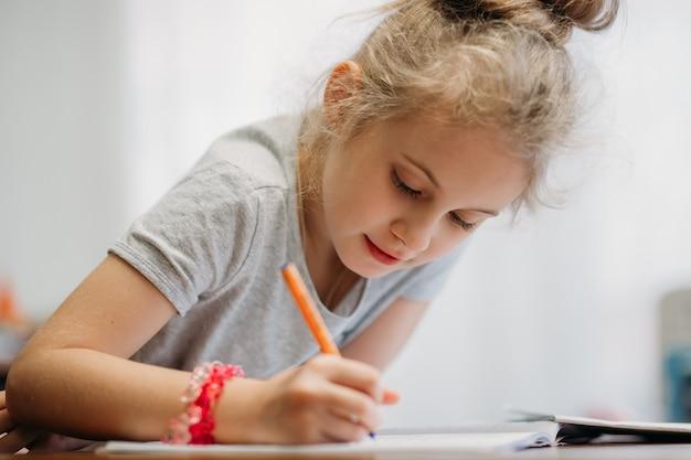 Une fillette de sept ans est assise à la maison à une table et écrit dans un cahier, accomplissant une tâche d'apprentissage ou répétant des leçons.