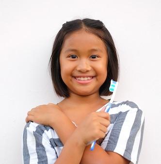 Fillette souriante tenant la brosse à dents sur fond blanc. belle fille sourit.
