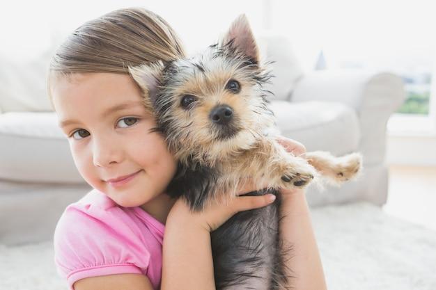 Fillette souriante tenant son chiot yorkshire terrier