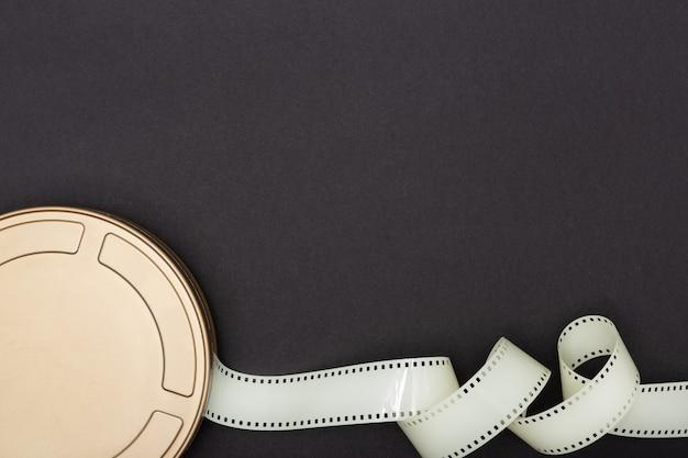 Film cinématographique peut, appareil photo argentique et bande de film sur fond noir. fond de film ou de télévision. vue de dessus espace copie