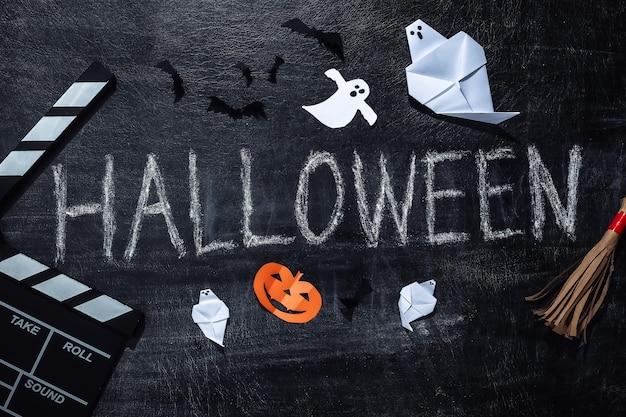 Film clap et chalk lettrage halloween sur un tableau noir avec décor helloween. thème halloween