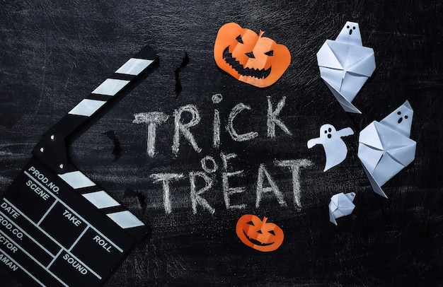 Film clapperboard et lettrage à la craie trick or treat sur un tableau à craie avec un décor helloween. thème halloween