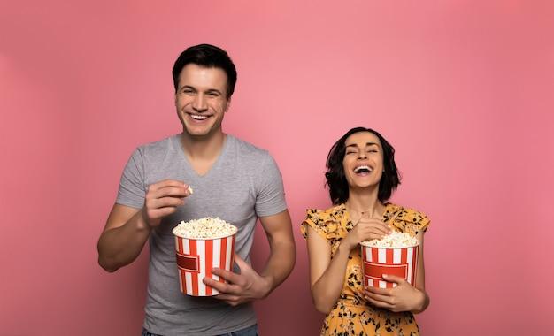 Film hilarant. heureux jeune couple, qui mange du pop-corn et rient ensemble en regardant des films.