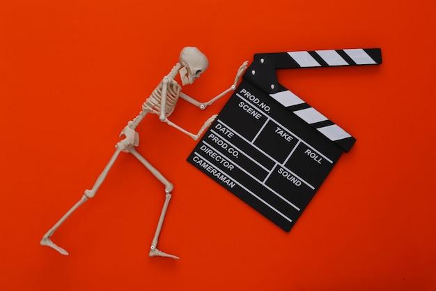 Film d'horreur, thème d'halloween. clap de cinéma et squelette décoratif sur orange