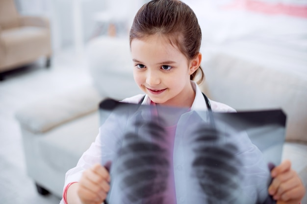 Film à rayons x. vue de dessus de l'adorable fille heureuse habile posant sur fond flou tout en regardant la radiographie et souriant