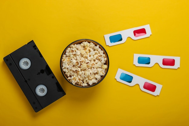 Film time anaglyphe stéréoscopique papier jetable lunettes 3d cassette vidéo et bol de pop-corn. vue de dessus