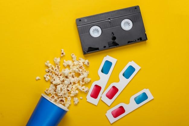 Film time seau en carton de cassette vidéo pop-corn et lunettes 3d en papier jetables anaglyphes stéréoscopiques. vue de dessus rétro des années 80