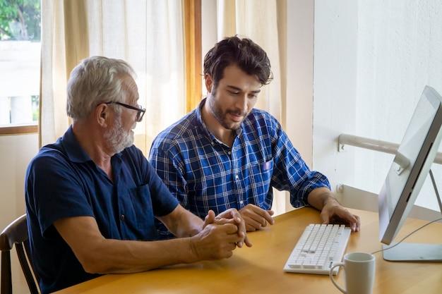 Fils adulte enseignant vieux père à l'aide d'un ordinateur