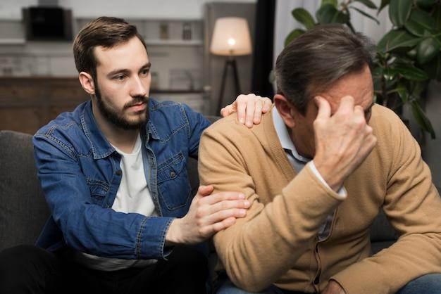 Fils adulte réconfortant père bouleversé