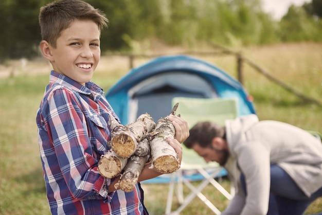 Fils aidant son père à allumer le feu de camp