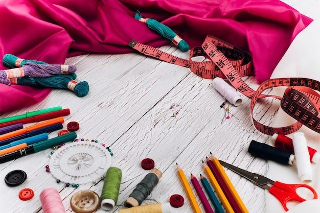 Fils, aiguilles, crayons, tissu, ruban à mesurer font un cercle sur une table en bois blanc