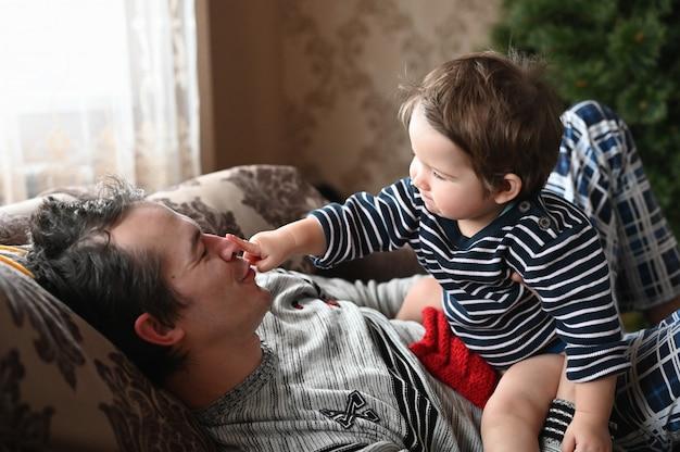 Le fils aime passer du temps avec son père. père et fils s'amusent. père seul à la maison avec un enfant jouant ensemble.