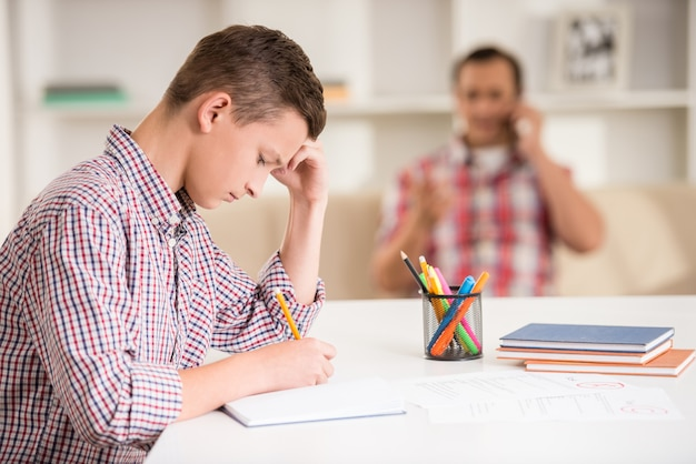 Fils assis au bureau pendant que son père parle au téléphone.