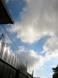 Fils barbelés contre un ciel nuageux