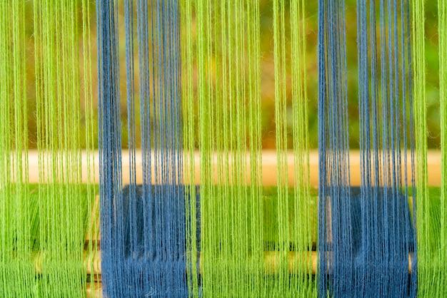 Fils bleus et verts dans une vieille machine en bois.