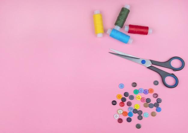 Fils et boutons multicolores sur fond rose.