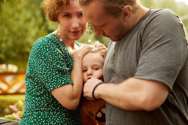 Fils de câlins en famille dans les arbres verts de la campagne