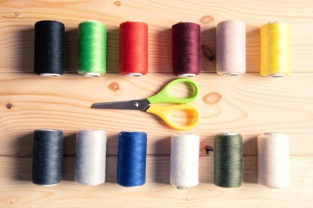 Fils et ciseaux multicolores sur une surface en bois