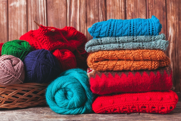 Fils de couleur, aiguilles à tricoter et vêtements sur la table en bois