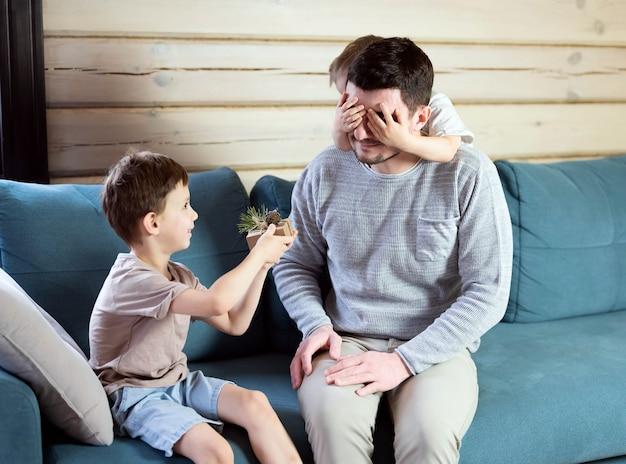 Le fils donne un cadeau à papa. papa et fils sur un canapé bleu dans une maison en bois. les enfants souhaitent à leur père une bonne année.