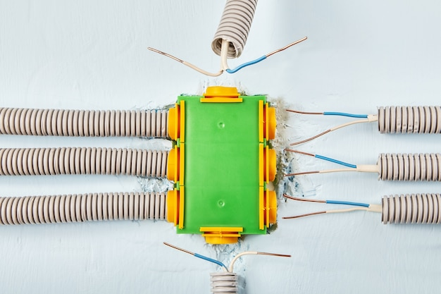 Les fils électriques domestiques sont cachés dans un conduit connecté à la boîte de distribution électrique.