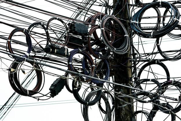 Fils électriques emmêlés sur poteau électrique urbain.