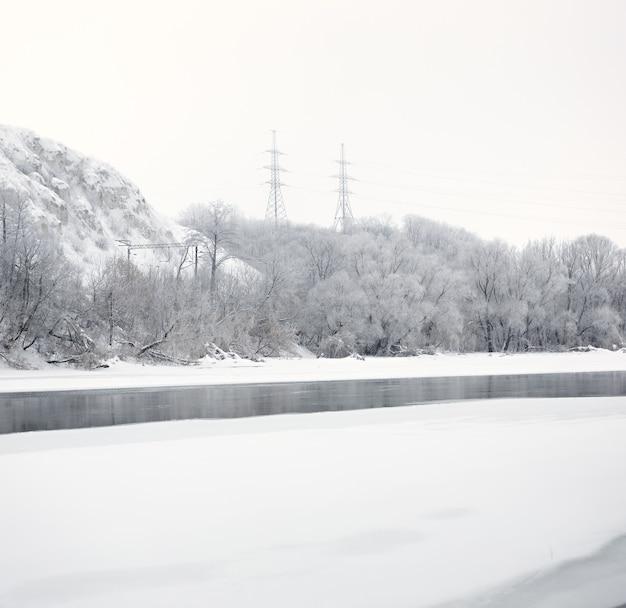 Fils électriques à haute tension de pilier sur les banques de la glace de rivière