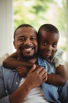 Fils embrassant son père à la maison