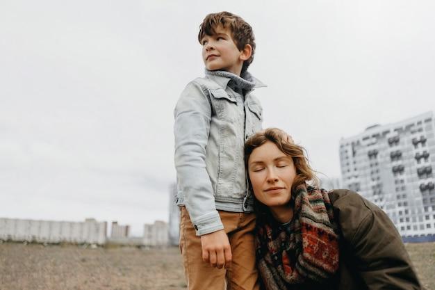 Fils embrasse sa mère. une mère satisfaite sourit dans les bras de son fils. le concept de relations familiales. changement de rôles dans la famille méléniale.