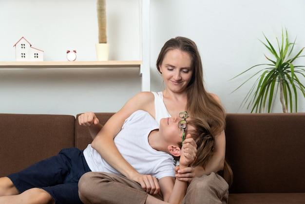Le fils est allongé sur les genoux de sa mère. jeune maman et adolescent parlant.