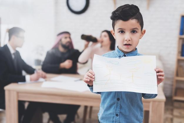 Le fils est debout avec un dessin heureux, la mère boit.