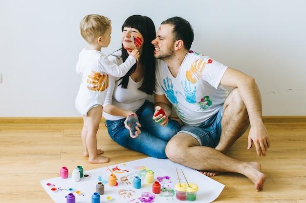 Fils de famille heureuse avec les parents et un chat peignant une affiche et l'autre avec des peintures