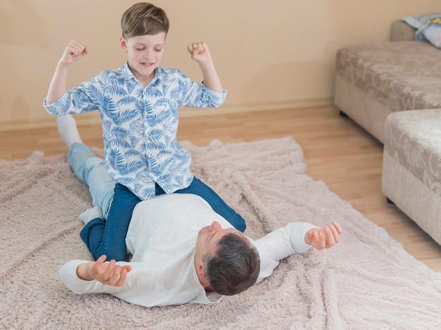 Fils de la fête des pères assis sur son père et jouant